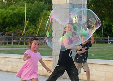 Children playing with giant bubble wand