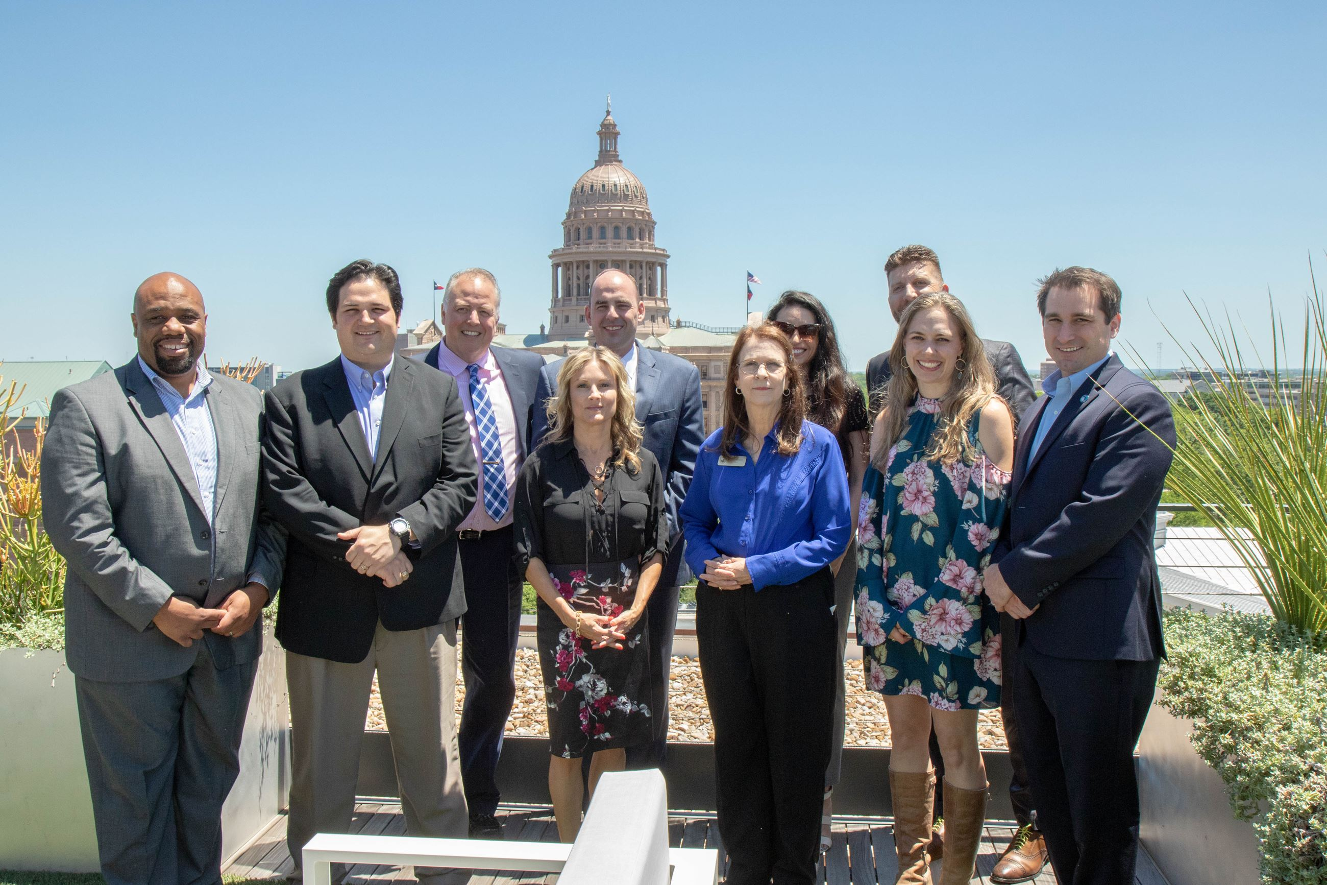 Members of City Staff, City Council, and the Chamber of Commerce pose in a group shot on a roof top