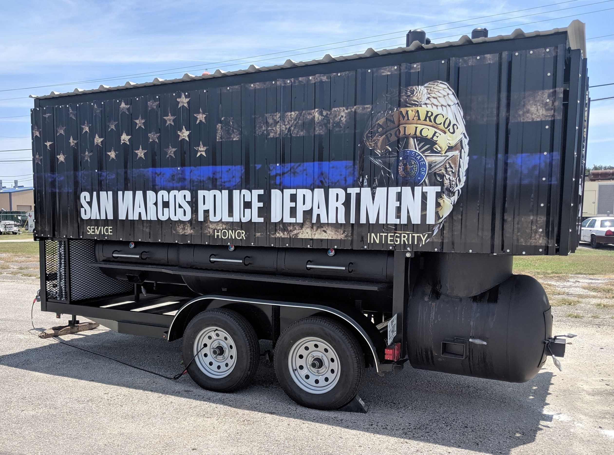 Large barbecue pit trailer with San Marcos Police Department logo on the outside