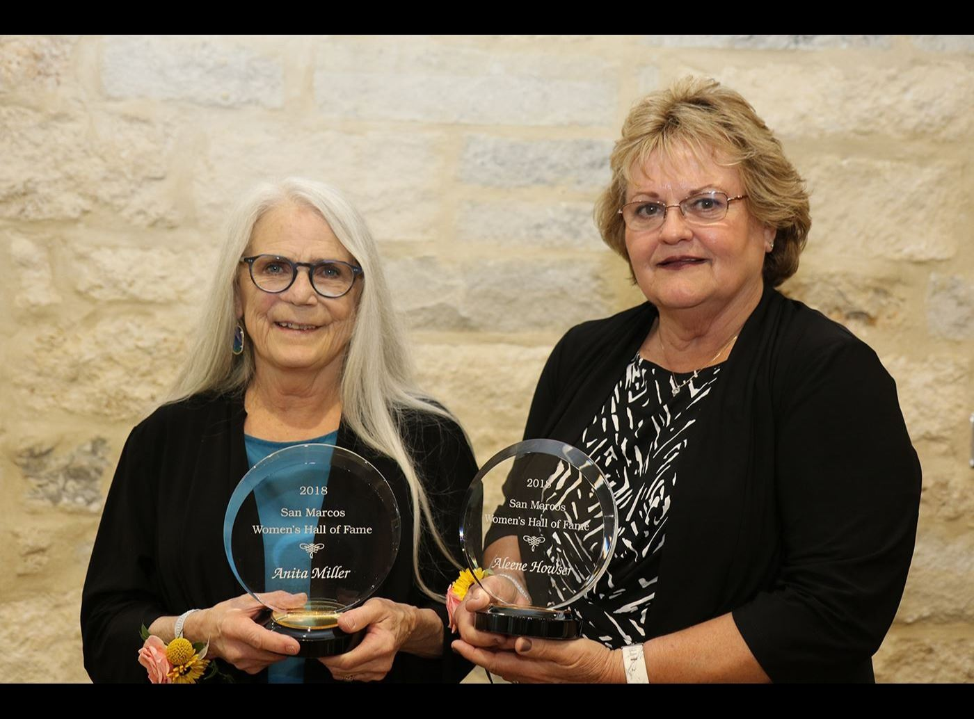Photo of two women holding awards