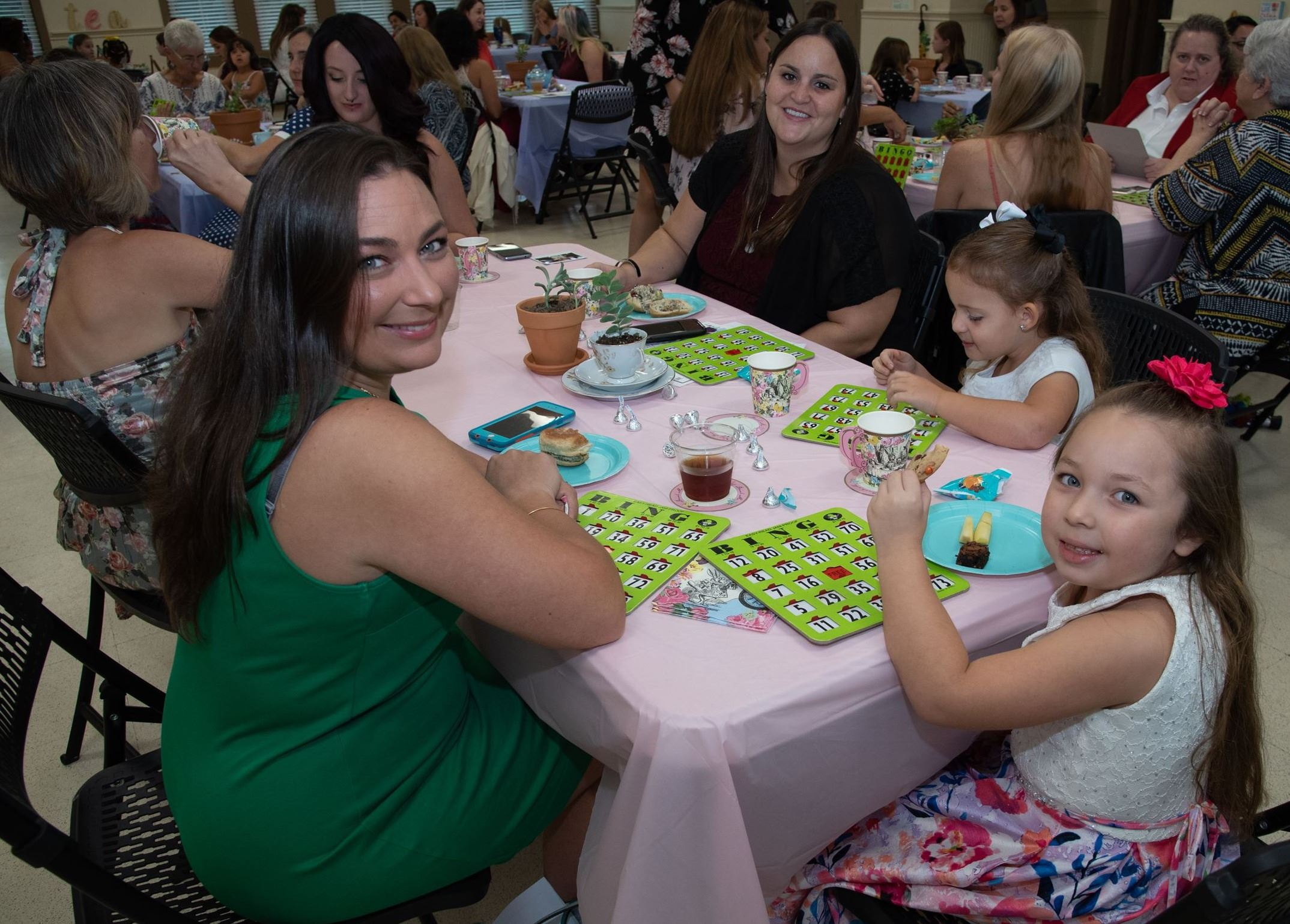 Photo of women around a table with games and refreshments during the 2018 Mother Daughter Tea event