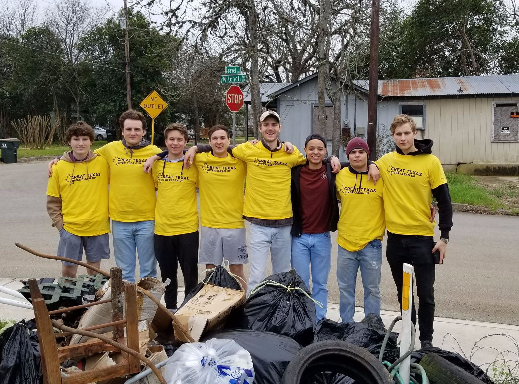 Group of volunteers standing behind pile of collected trash from clean-up
