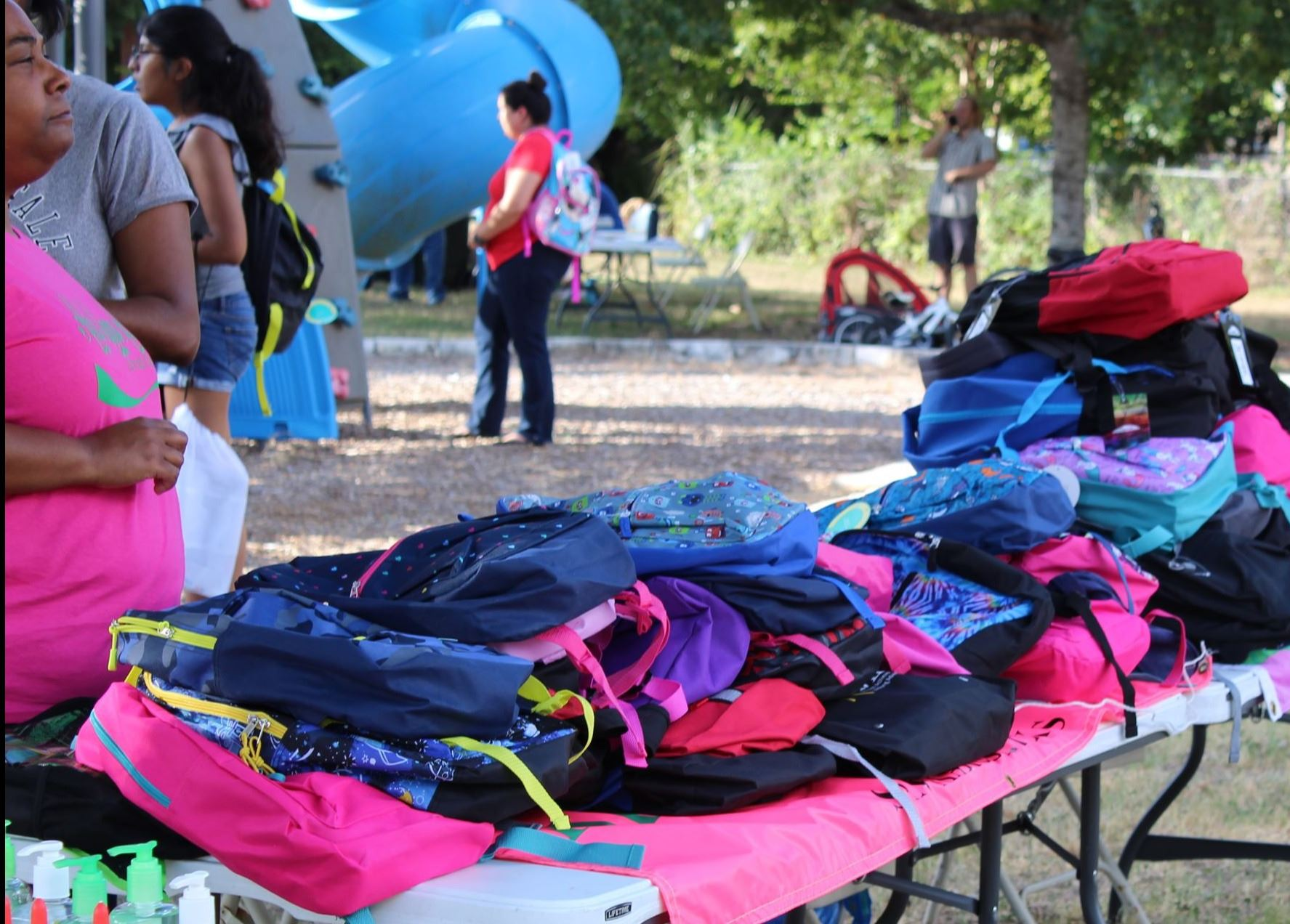 Photo of backpack giveaway form 2019 with table full of supplies and families standing around