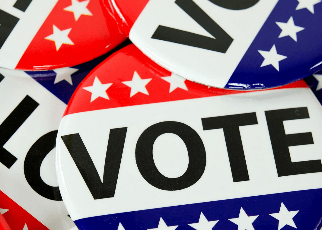 "Image of stack of red, white and blue election buttons with the word ""vote"" on them."