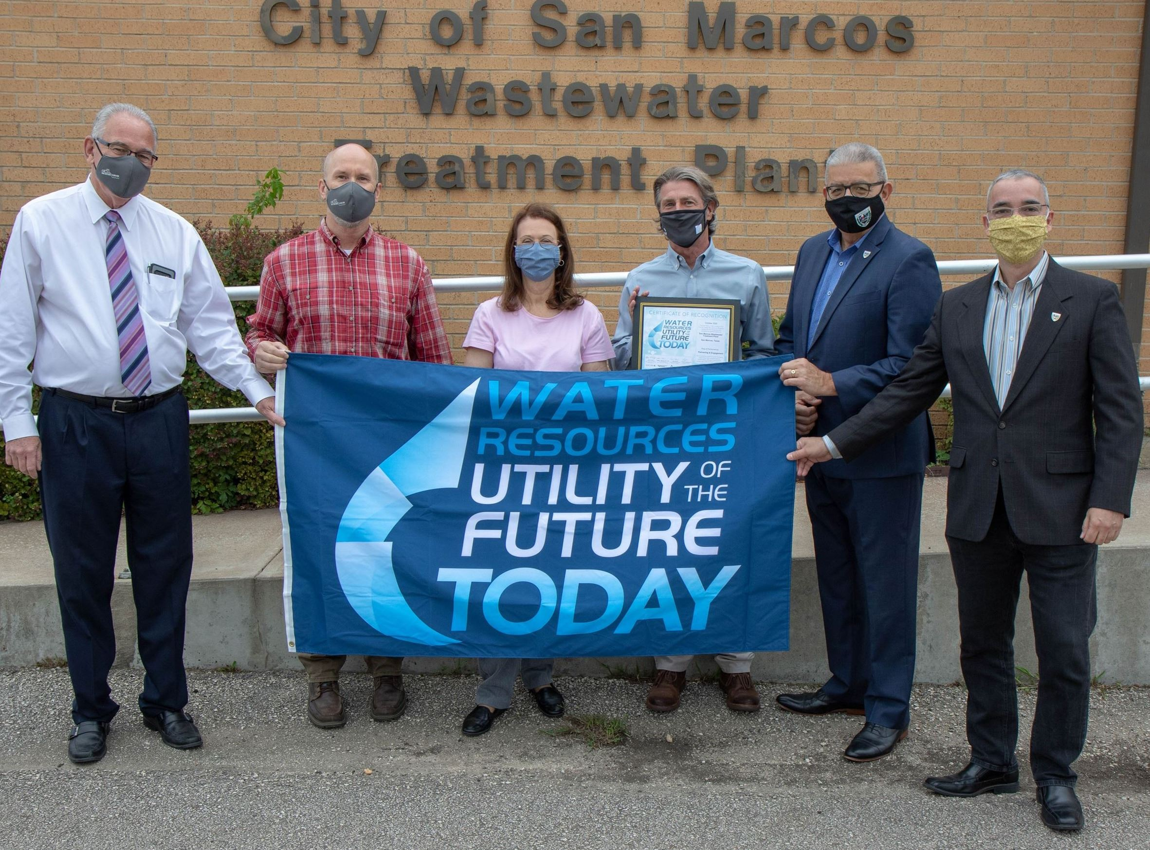 Photo of elected officials and WWTP representatives holding award banner in front of WWTP.