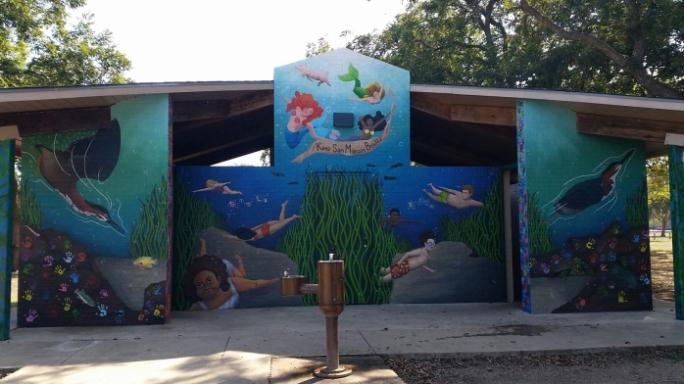 Mermaid and sea life mural painted on a park building