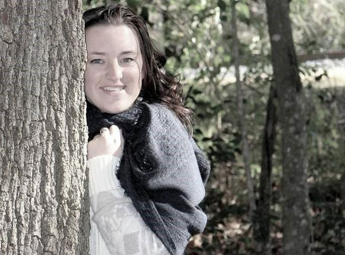 Erin McCann hugging a tree and smiling