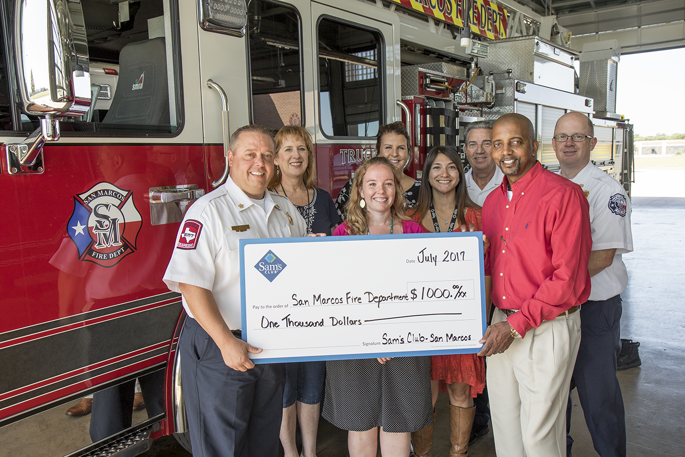 Sam&#39s Club Associates and San Marcos Fire Department accepts donation check.