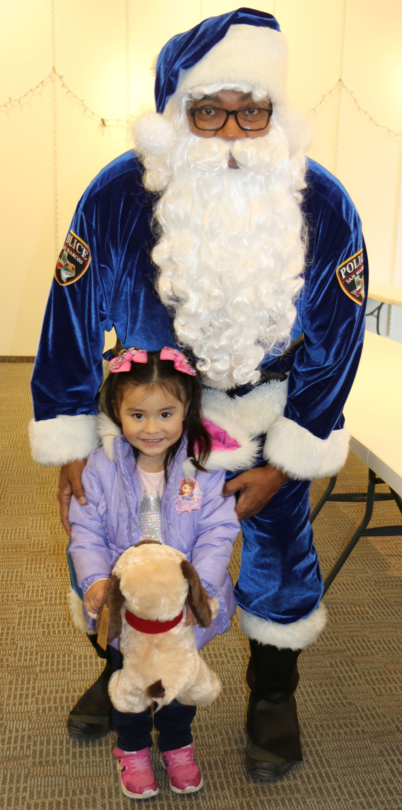 Blue Santa poses with child holding stuffed animal
